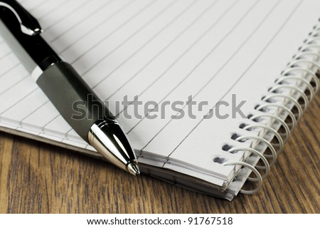 Pen and notepad on wooden table - stock photo