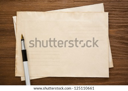 pen and old postal envelope on wood texture - stock photo