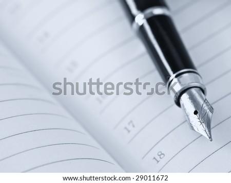 Pen and organizer,blue-toned,shallow DOF - stock photo