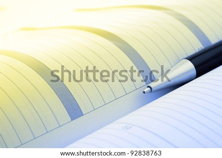 Pen and organizer close-up toned in yellow and blue color - stock photo