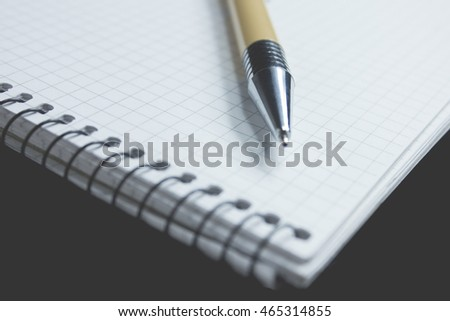 Pen and paper in the black background