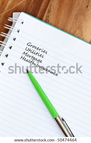 Pen and paper with list of monthly expenses. - stock photo