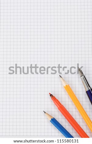 pen and pencil on checked school paper of notepad - stock photo