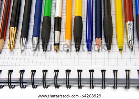 pen and pencils on notebook isolated on white background - stock photo