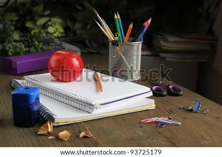 pen and red apple on a note book