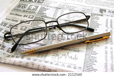Pen and spectacles on financial page of newspaper