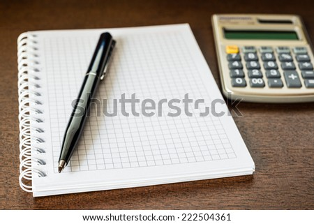 Pen and the calculator on the table