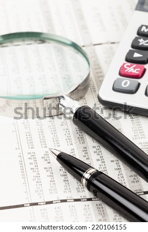 Pen, calculator, and magnifier rest on stock price detail financial newspaper - stock photo