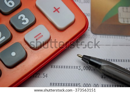 pen ,calculator, credit card on account book. selective focus on pen - stock photo
