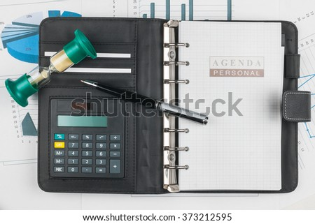 Pen, calculator on notebook and hourglass, on charts and graphs - stock photo
