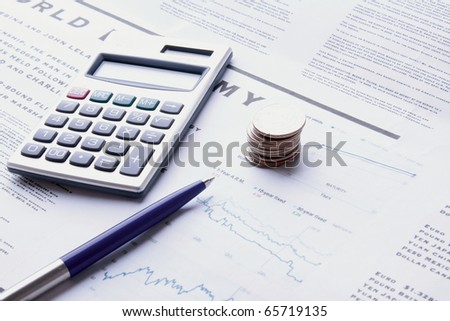 pen, coins and calculator on business paper - stock photo