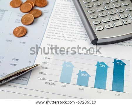 Pen, coins and calculator on the home sales chart - stock photo