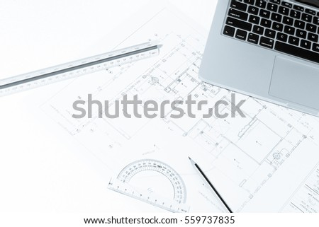 Pen, drawing rulers, and notebook over house construction blueprint with blue tone effect, useful for construction, business, architecture, engineering, insurance background concepts