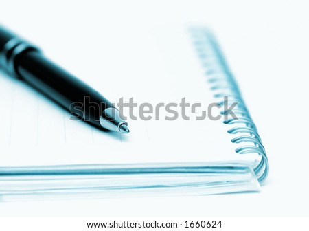 Pen (focus on the top) and note pad, shallow DOF and blue toned
