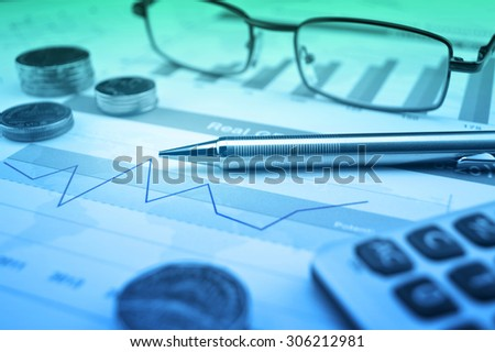 Pen, gasses, coin and calculator on financial chart and graph, accounting background - stock photo