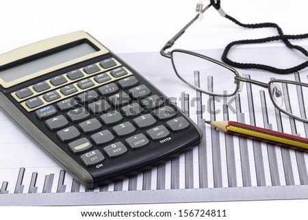Pen, glasses and calculator on paper table with finance diagram  - stock photo