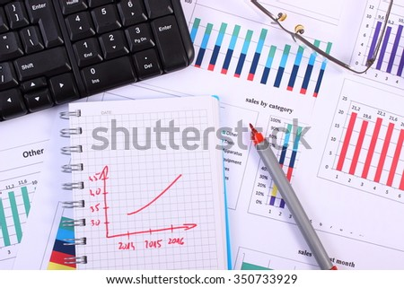 Pen, glasses and computer keyboard on financial chart, business concept, analysis of sales plan, business report, business work station with paperwork