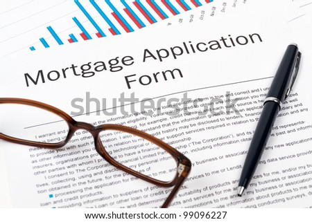 Pen, Glasses and Mortgage Application Form on desktop in business office.