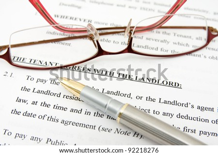 pen,glasses and tenant agreement with the landlord - stock photo