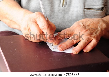 Pen in an old person's hand, writing on white paper - stock photo