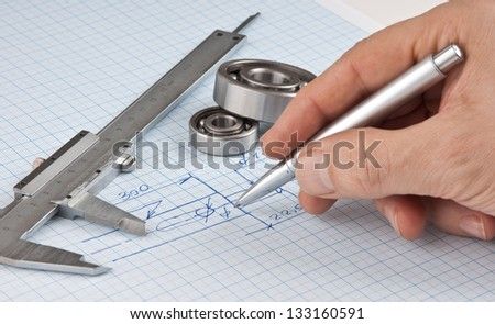 pen in hand and  technical drawing on graph paper - stock photo