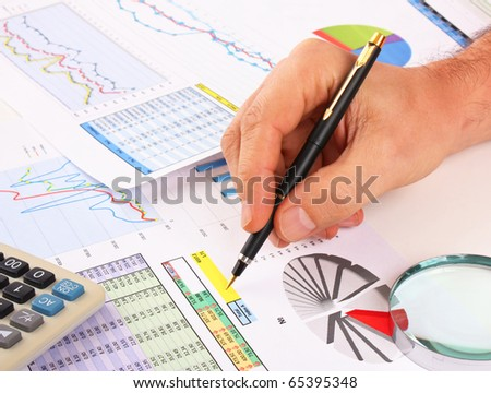 pen in hand and working paper chart