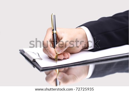 pen in hand writing on the page and reflection