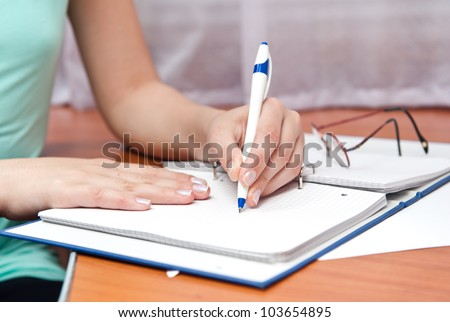 pen in left hand writing on the notebook - stock photo