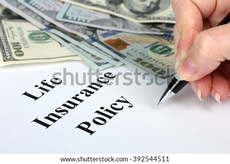 """pen in woman hand and Bank notes lying on the paper with the words """"life insurance policy"""" - stock photo"""