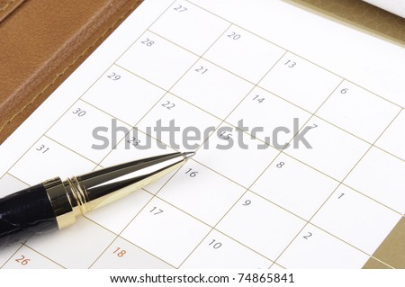 Pen laying on a calendar reading to make entries into the dates for appointments and future commitments - stock photo