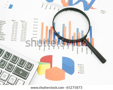 Pen, magnifying glass and calculator on paper table with diagram - stock photo