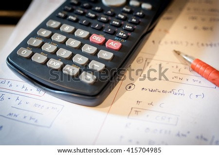 Pen, notepad, and calculator - stock photo