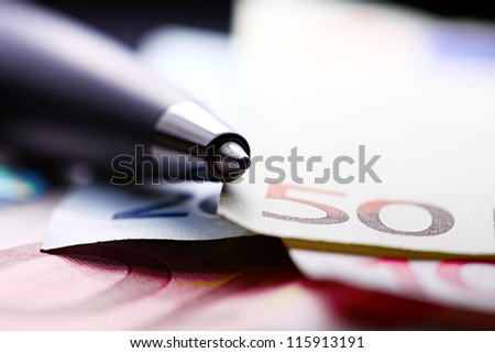 Pen on a euro banknotes. Macro image with selective focus.