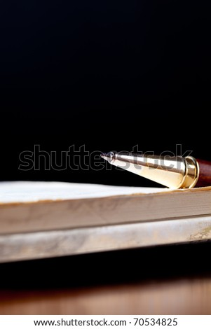 Pen on a notebook over a dark background - stock photo