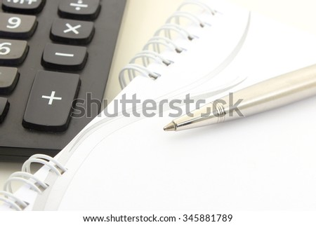 pen on a notebook with calculator on a white isolated screen - stock photo