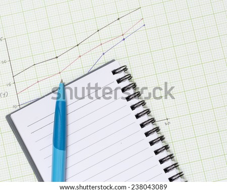 Pen on blank note book with graph paper background. - stock photo