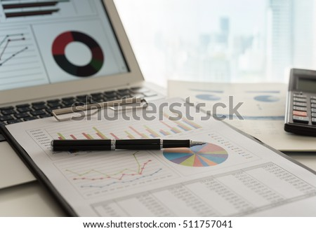 Pen on business graphs report, computer on desk of financial advisor. Accounting background abstract concept.