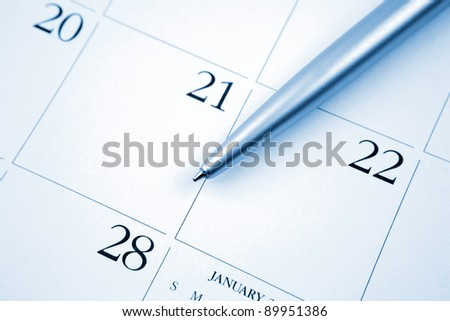 Pen on calendar page - stock photo