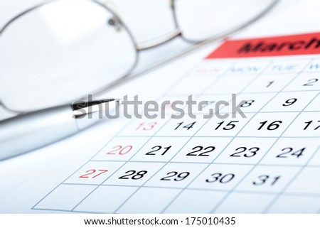 Pen on calendar page closeup  - stock photo