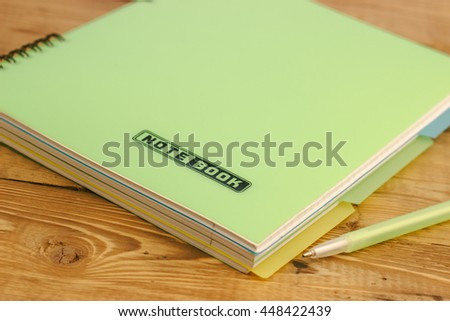pen on the closed notebook lying on a wooden table - stock photo