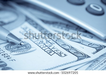 Pen on the hundred-dollar bills and cropped calculator - blue toned image - stock photo