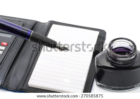 pen on top of notepad with opened ink bottle, blur background - stock photo