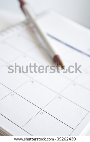 Pen over calendar sheet  Focus on the sheet - stock photo