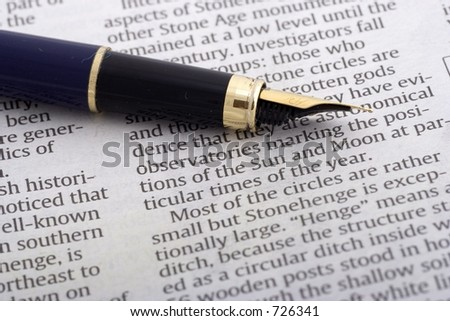 Pen over newspaper close up - stock photo