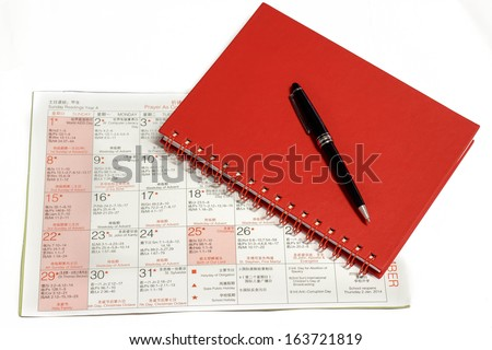 Pen over notebook on Christmas calendar isolated on white background. - stock photo