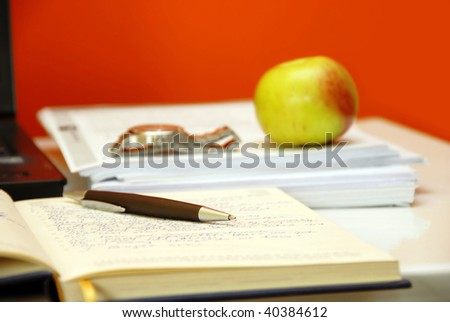 pen over organizer on working desk over orange background - stock photo