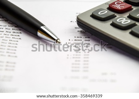 Pen point on bank statement with calculator