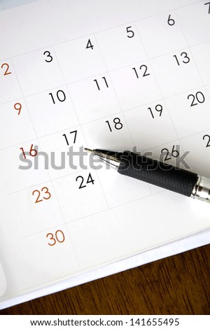 pen point to date on calendar - stock photo