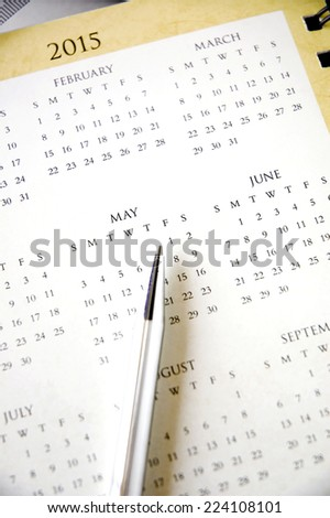 pen point to international worker day on calendar - stock photo