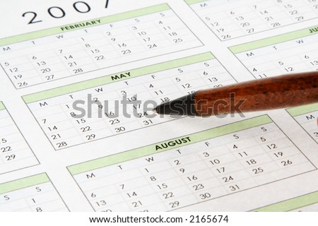 Pen pointing to a date on a calendar